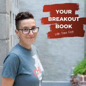 Your Breakout Book Podcast with Dana Kaye looking at the camera while standing next to a cement wall.