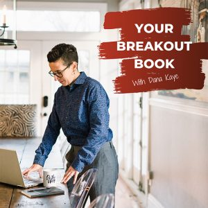 Your Breakout Book Podcast with Dana Kaye standing at a table looking at laptop and wearing a blue button down shirt.